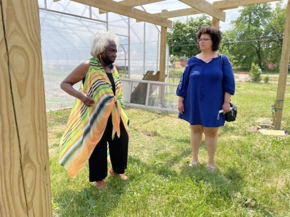 Two women stand under a pergola in a green area beside a greenhouse. The women are Vel Scott and Shani Richards.