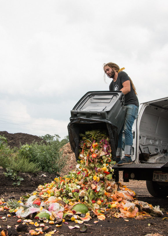 A man stands on the back of a van and unloads a dumpster full of food waste on to the ground. The good waste includes scraps like watermelon rind, tomato cores, and pineapple tops among other things.